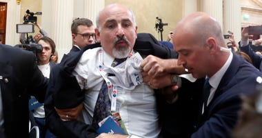 Security staff push out a man after a scuffle prior to a press conference after the meeting of U.S. President Donald Trump and Russian President Vladimir Putin at the Presidential Palace in Helsinki, Finland, Monday