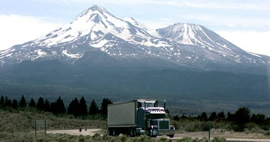 In this June 19, 2008, file photo a truck drives past Mount Shasta near Weed, Calif. California and 14 other states are suing the Trump administration over its decision to suspend an Obama-era rule aimed at limiting pollution from trucks. The lawsuit file