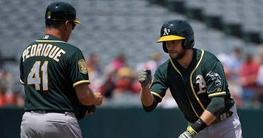 Oakland Athletics' Jed Lowrie, right, is congratulated by first base coach Al Pedrique after hitting a double for his 1,000th career hit during the first inning of a baseball game against the Los Angeles Angels, Sunday, Aug. 12, 2018, in Anaheim, Calif. (