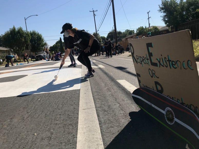 Activists paint large letters in white on a street in San Jose.