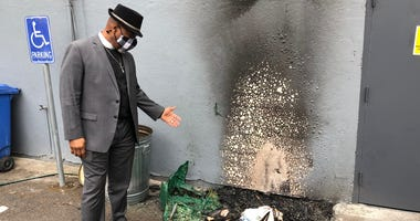 Senior Pastor Mike McBride shows the spot outside his church that was damaged by a suspected arson fire Wednesday.