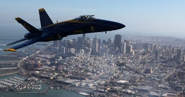 A U.S. Navy Blue Angels F/A-18 Hornet piloted by U.S. Marine Corps Major Nathan Miller flies over the San Francisco skyline during a practice flight in Fleet Week 2009.