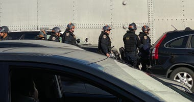 A group of officers in riot gear walk on to the Bay Bridge.