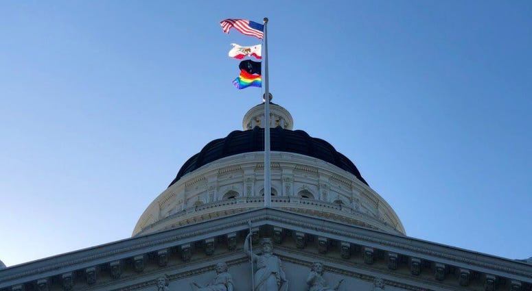The LGBTQ pride flag flies at the California state capitol in Sacramento on June 17, 2019.