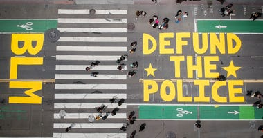 "An overhead look at a ""Defund The Police"" mural in front of San Francisco City Hall."