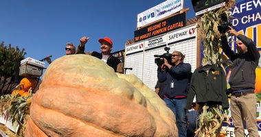 Leonardo Urena celebrates winning $15,000 and a stay in a Ritz Carlton after winning the heaviest pumpkin contest in Half Moon Bay on Oct. 14, 2019 with a specimen weighing 2,175 pounds.