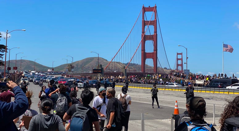 Black Lives Matter protesters march across and on to the roadway at the Golden Gate Bridge.
