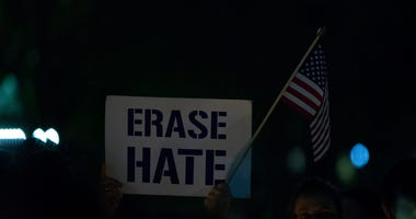 WASHINGTON, DC - OCTOBER 27: A vigil participant holds a 'Erase Hate' sign during a Havdalah vigil for the victims of the Tree of Life Congregation shooting in front of the White House on October 27, 2018 in Washington, DC.