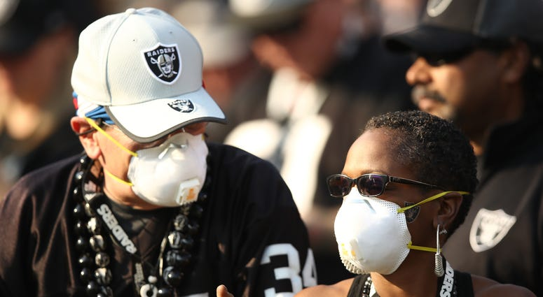 Fans wear face masks in the stands during the NFL game between the Oakland Raiders and the Los Angeles Chargers at Oakland-Alameda County Coliseum on November 11, 2018 in Oakland, California.