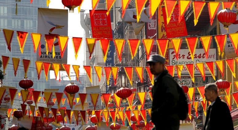 edestrians walk by red and yellow banners that are strung across Grant Street for Chinese New Year in San Francisco's Chinatown district on February 3, 2011