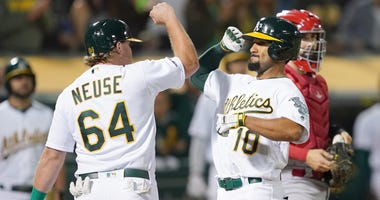 Marcus Semien #10 of the Oakland Athletics is congratulated by Sheldon Neuse #64 after Semien hit a two-run home run against the Los Angeles Angels of Anaheim in the bottom of the fifth inning at Ring Central Coliseum on September 04, 2019 in Oakland.
