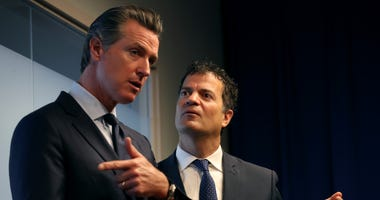 California Gov. Gavin Newsom (L) talks with California environmental agency secretary Jared Blumenfeld (R) during a news conference at the California justice department on September 18, 2019 in Sacramento, California.