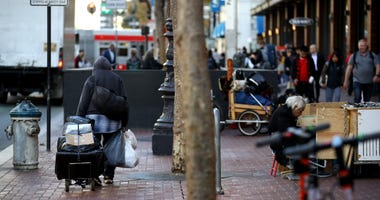 A homeless man spulls a cart with his belongings on November 25, 2019 in San Francisco.