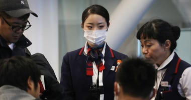A Japan Airlines worker (C) wears a face mask while working inside a terminal at Los Angeles International Airport on Jan. 23, 2020.