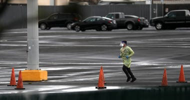 SAN MATEO, CALIFORNIA - MARCH 16: A medical worker runs across the parking lot during a coronavirus drive-thru test clinic at the San Mateo County Event Center on March 16, 2020 in San Mateo, California.