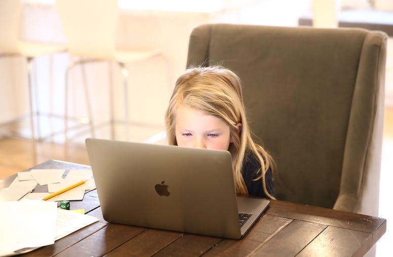 Evianna Van Santvoord, who is in kindergarten, does her schoolwork at home on March 18, 2020 in San Anselmo, California.