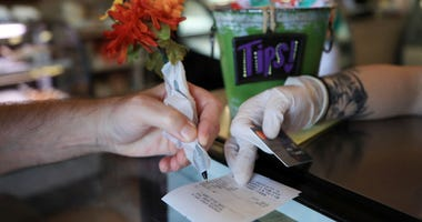 NEW ORLEANS, LA - MARCH 19: A patron uses a pen wrapped in paper to sign a credit card receipt at Angelo Brocato's Italian Ice Cream Parlor due to the coronavirus (COVID-19)