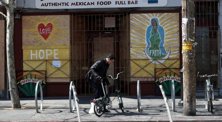 cyclist parks his bicycle in front of a business that has the windows covered with plywood on Valencia Street on March 20, 2020 in San Francisco