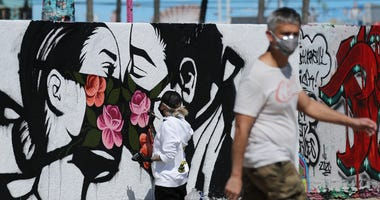 Artist Pony Wave paints a scene depicting two people kissing while wearing face masks on Venice Beach on March 21, 2020 in Venice.