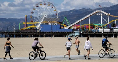 SANTA MONICA, CALIFORNIA - MARCH 21: People exercise on Santa Monica beach in front of the shuttered Santa Monica Pier on March 21, 2020 in Venice, California.