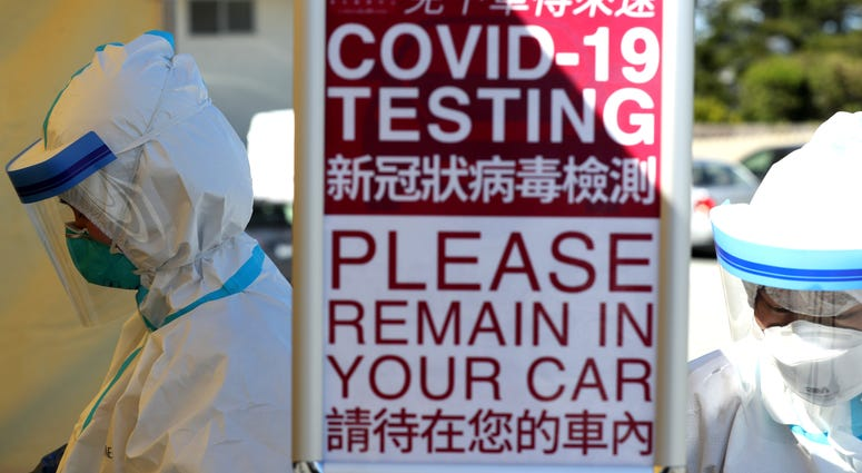 Medical professional wait to administer a coronavirus (COVID-19) test during a drive-thru testing station on March 26, 2020 in Daly City.