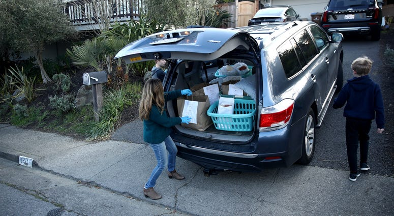 : Lelah Nichol, the wife David Nichol, the owner of Sociale, delivers meals with her two sons, Julian and Ellis, on March 27, 2020 in San Francisco.