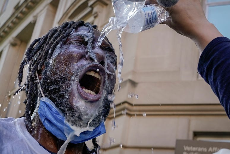 A demonstrator is doused with water and milk after being hit with pepper spray from law enforcement during a protest on June 1, 2020 in downtown Washington, DC.