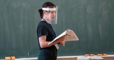 A teacher wearing a plastic face visor teaches a class at Kinugawa Elementary School on June 3, 2020 in Nikko, Japan.