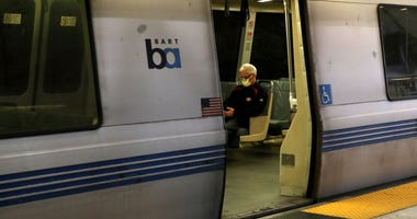 SAN FRANCISCO, CALIFORNIA - APRIL 08: A Bay Area Rapid Transit (BART) passenger rides in an empty train car on April 08, 2020 in San Francisco, California.