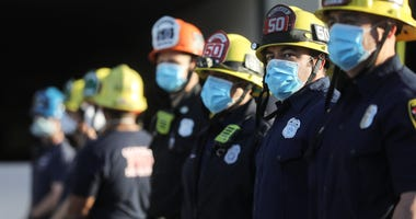 GLENDALE, CALIFORNIA - APRIL 16: Firefighters wear face masks as they stand and pay tribute to healthcare workers during a shift change at Glendale Memorial Hospital amid the coronavirus pandemic on April 16, 2020 in Glendale, California.