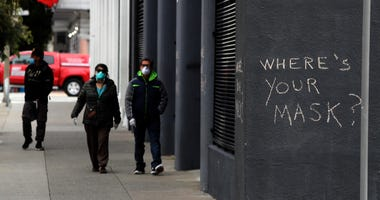 SAN FRANCISCO, CALIFORNIA - APRIL 20: Pedestrians walk by graffiti encouraging the wearing of masks on April 20, 2020 in San Francisco, California.