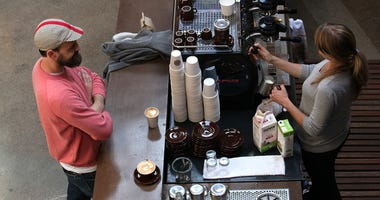 A barista (R) at Sightglass Coffee makes a coffee drink for a customer on August 26, 2011 in San Francisco, California.