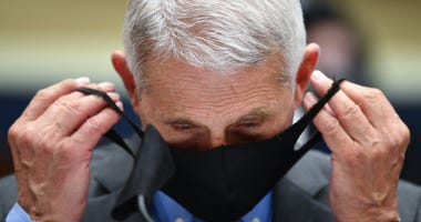 Dr. Anthony Fauci, director of the National Institute of Allergy and Infectious Diseases, takes off his face mask before testifying at a hearing of the U.S. House Committee on Energy and Commerce on Capitol Hill on June 23, 2020 in Washington, DC.