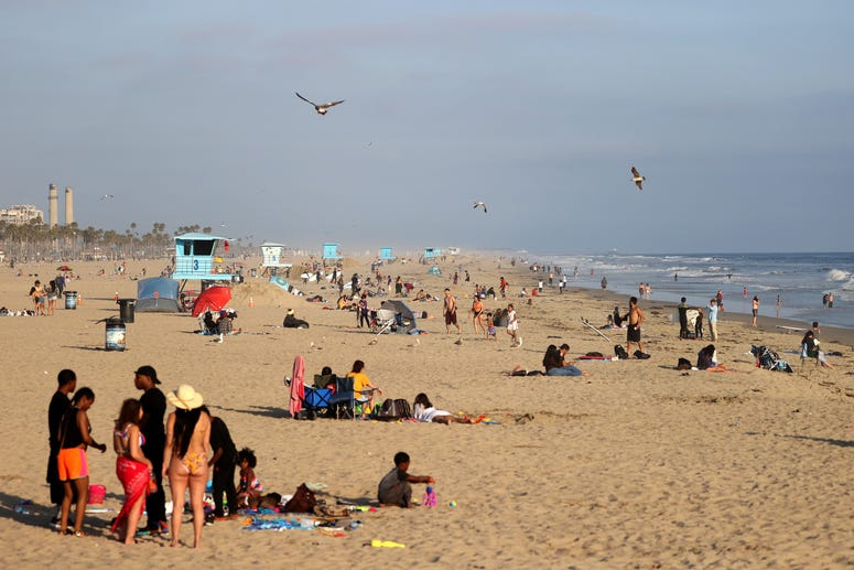 HUNTINGTON BEACH, CA - APRIL 30: People gather at the beach on April 30, 2020 in Huntington Beach, California.