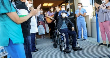 CORONADO, CALIFORNIA - MAY 08: (EDITORIAL USE ONLY) Isaias Perez Yanez, 59, is applauded by hospital staff as he is released from Sharp Coronado Hospital after battling COVID-19 for five weeks there on May 8, 2020 in Coronado, California.