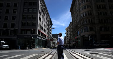 SAN FRANCISCO, CALIFORNIA - MAY 15: A U.S. Postal Service letter carrier stands in the middle of Powell Street on May 15, 2020 in San Francisco, California.