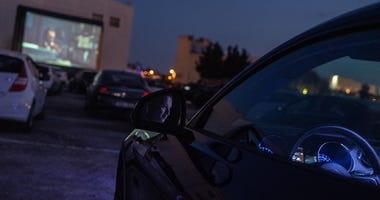 People watch 'Joker' movie from their cars at a temporary drive-in theatre held in a disco club car park amid the ongoing Covid-19 pandemic on May 30, 2020 in Golmes, near Barcelona, Spain.