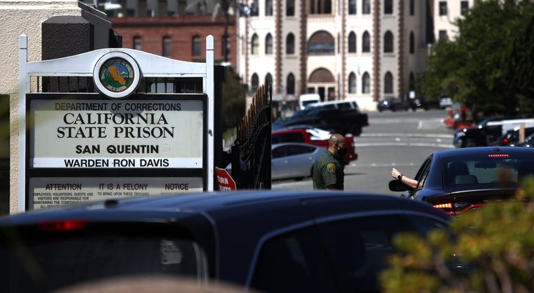A California Department of Corrections and Rehabilitation (CDCR) officer wears a protective mask as he stands guard at the front gate of San Quentin State Prison on June 29, 2020 in San Quentin, California.