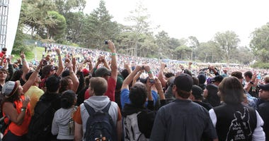 Music fans rush onstage to dance with musician Tom Morello of The Nightwatchman as he performs onstage at the Sutro Stage during Day 3 of the 2012 Outside Lands Music and Arts Festival at Golden Gate Park on August 12, 2012 in San Francisco, California.
