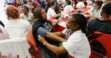 Alice Rainwater (C) get her blood pressure checked by licensed vocational nursing student Alisa Humphrey (R) as part of a free health care service at the Care Harbor clinic at the Los Angeles Sports Arena on September 27, 2012 in Los Angeles.