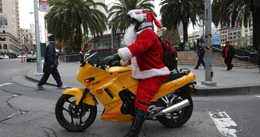 A man dressed as Santa Claus rides a motorcycle in Union Square on December 14, 2012 in San Francisco.