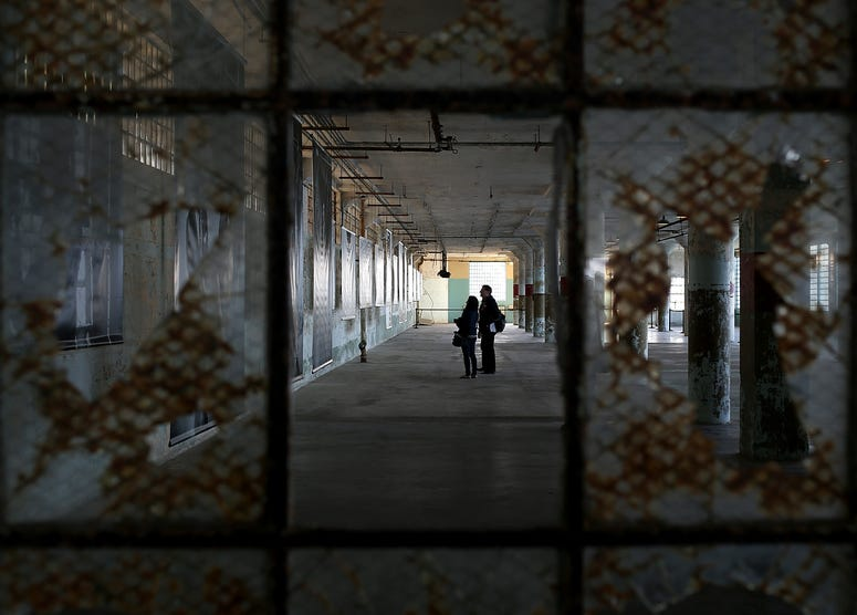 Reporters view an exhibit of photographs documenting the last day of Alcatraz federal penitentiary on March 21, 2013 in San Francisco, California.