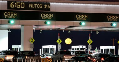 The moon sets as traffic backs up at the San Francisco-Oakland Bay Bridge toll plaza while commuters make their way into San Francisco on the first day of the (Bay Area Rapid Transit) BART strike on October 18, 2013 in Oakland, California.