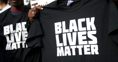 "SAN FRANCISCO, CA - DECEMBER 18: A protester holds a black lives matter t-shirt during a ""Hands Up, Don't Shoot"" demonstration in front of the San Francisco Hall of Justice on December 18, 2014 in San Francisco, California."