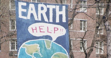 A crowd of people gather near a large poster that shows a speach bubble from planet Earth that reads 'Help!!', on the occaision of the first Earth Day conservation awareness celebration, New York, New York, April 22, 1970.