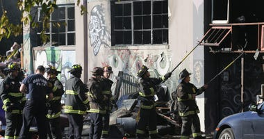 Firefighters work to clear debris at the site of the Ghost Ship warehouse in Oakland where 36 people died in a fire in 2016.