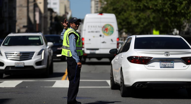 21: A San Francisco Municipal Transportation Agency officer directs traffic at an intersection with street lights out during a citywide power outage on April 21, 2017 in San Francisco, California.