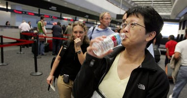 A United Airlines passenger takes a sip of water before throwing away the bottle at a security checkpoint at San Francisco International Airport August 10, 2006 in San Francisco.