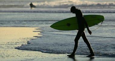 SAN FRANCISCO - DECEMBER 05: A surfer walks out of the water at Ocean Beach December 5, 2006 in San Francisco, California.