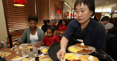 Denny's waitress Fong Van Luben (R) delivers free Grand Slam breakfasts to customers February 3, 2009 in Emeryville, California.